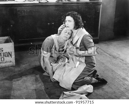 Two women sitting on the floor while one is holding the other