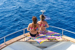 Two women sitting on the front forward deck of the ship in a sunny summer day on vacation holiday