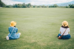Two women sitting on the grass field, looking to beautiful view and keep space for avoid spreading of virus disease in covid-19 pandemic. Social distancing puts space between people.
