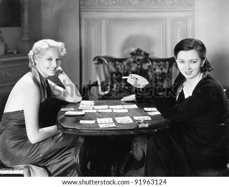 Two women sitting together playing cards