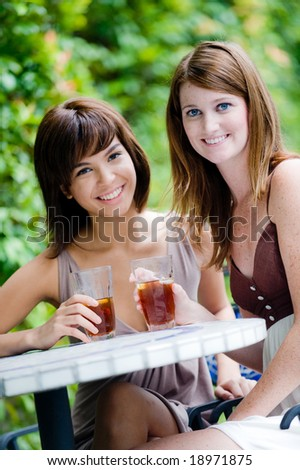 Two women sitting together with glasses of ice tea