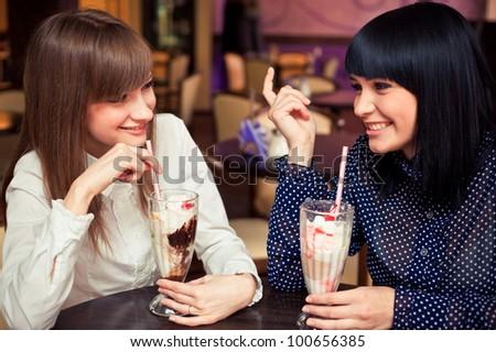 two women speaking in caffee