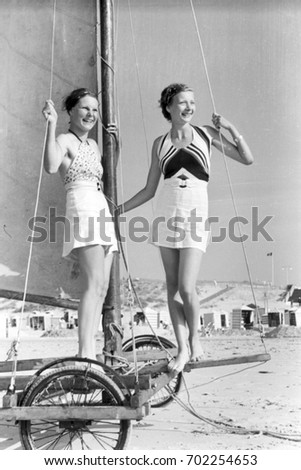 Two women standing on land yacht on beach