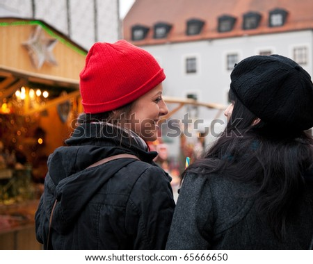 Two women strolling over Christmas market in front of a booth, it is cold