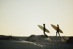 Two women surfers carrying surfboards and walking towards the sea. Female friends going on water surfing in the ocean.