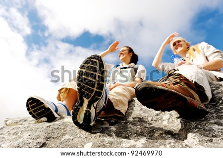 two women take a break from trekking and rest on a rock outdoors - stock photo