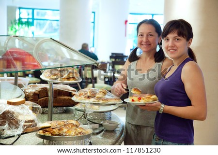 Two women takes fresh pastry on table in buffet