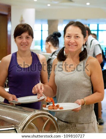 Two women  takes sausages in hotel buffet