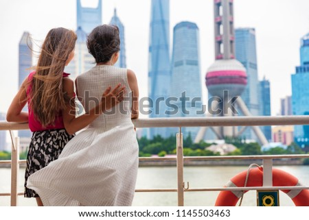 Two women taking the ferry in Shanghai city, China, crossing the Bund river looking at the view of famous pearl tv tower, landmark. Travel people lifestyle. #1145503463