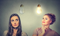 Two women thinking looking up at light bulbs isolated on grey wall background. Human face expressions, emotions, perception. Cognitive skills ability concept