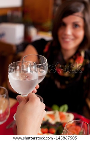 Two women toasting in a restaurant with wineglasses filled with chilled mineral water, focus to the glasses