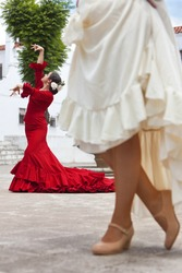 Two women traditional Spanish Flamenco dancers dancing in a town square, the focus is on the dancer in the red dress