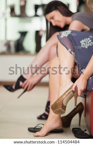 Two women trying on shoes in a boutique
