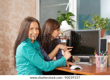 Two women using computer in office or home - stock photo