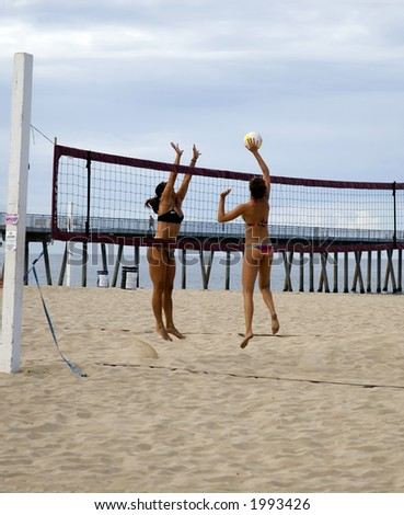 two women volleyball players battle it out at the net on a court at the beach in their bikinis