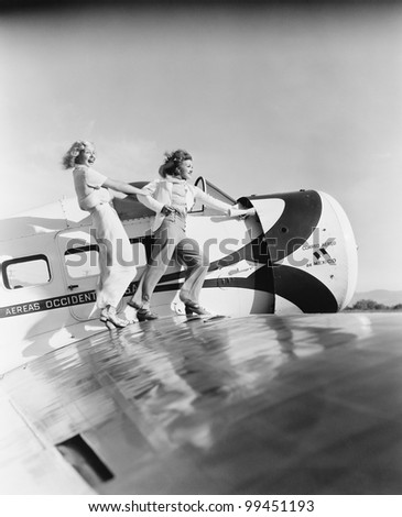Two women walking on the wing of a plane