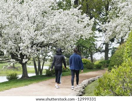 two women walking through beautiful park