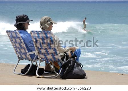 Two women watch surfers on the South Shore of Oahu. #556223