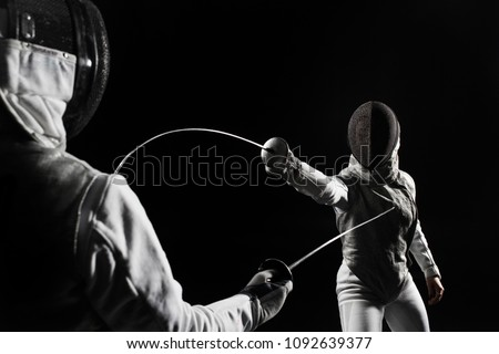 two women wearing helmets and white uniforms fencing on black background