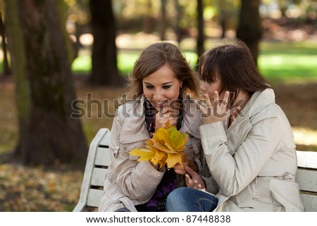 Two women whispering and smiling at the city park