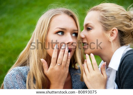 Two women whispering and smiling at the city park. Sitting on green grass