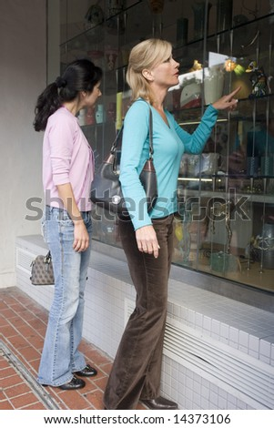 Two women window shopping on a city street