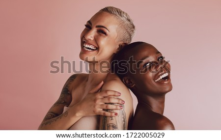 Two women with buzz cut hairstyle standing back to back and smiling at camera. Female models with beautiful skin smiling together over beige background.