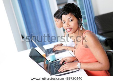 Two women with laptops doing business or trading online with focus on pretty girl looking up