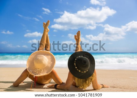 Two women with strasw hat suntanning #1041781909