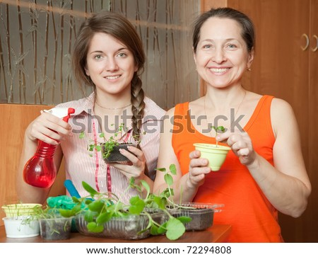 Two women with various sprouts at home