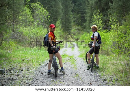Two womens on mountain bikes on old road in forest