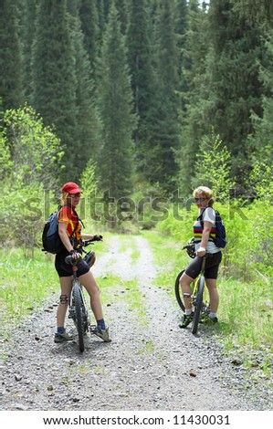 Two womens on mountain bikes on old road in forest - stock photo
