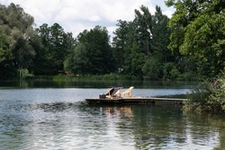 Two wood-framed deckchairs on a jetty at Weßlinger See (Lake Weßling) in Upper Bavaria in Germany on a summer day