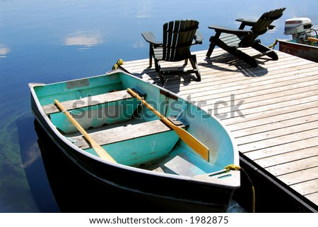 Two wooden adirondack chairs on a boat dock on a beautiful still lake with sky reflection