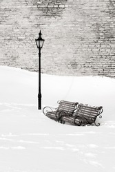 Two wooden and metal park benches in deep white snow near street lantern at winter. Limestone wall in the background.