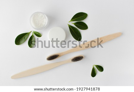 two wooden bamboo eco friendly toothbrushes, dentifrice and green leaves on white background.  Photo stock ©