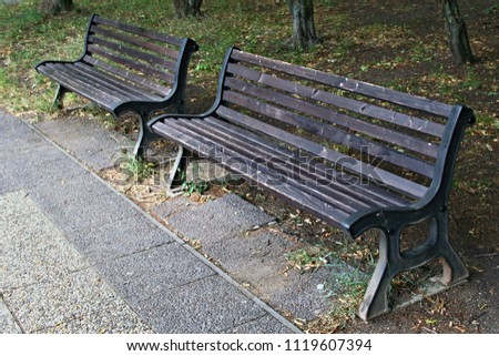 Two wooden benches at the pavement a park #1119607394