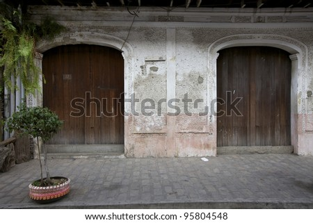 Two wooden carriage doors in stucco wall on sidewalk