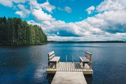 Two wooden chairs bench on a wood pier overlooking a blue lake water with green forest and cloud sky in Finland