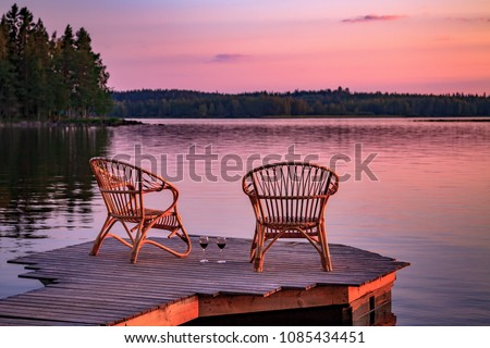 Two wooden chairs on a wood pier overlooking a lake at sunset in Finland