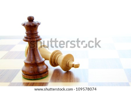 Two wooden chess pieces alone on a chess board.