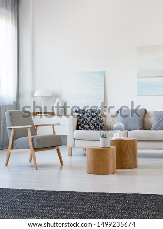 Two wooden coffee tables with plant in pot in front of grey corner sofa in fashionable living room interior #1499235674