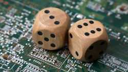Two wooden dice on a green circuit board. Random numbers.