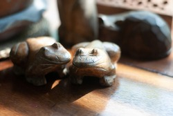 Two wooden frogs places together on the table with sunlight shining to them from the glass window, its background is wooden table
