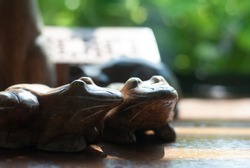 Two wooden frogs places together on the table with sunlight shining to them from the glass window, its background is blurred green plant