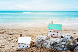 Two Wooden houses model on the rock and sand with blurred seascape background, Christian concept wise man build house on the rock but foolish man built house on the sand