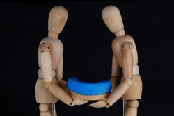 two wooden men hold an imprint of a model with silicone on a black background