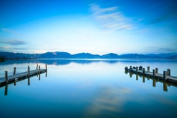 Two Wooden pier or jetty on a blue lake sunset and cloudy sky reflection on water. Long exposure, Versilia Massaciuccoli Lake, Tuscany, Italy.
