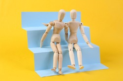 Two Wooden puppets hug on stairs podium, yellow background. Concept art, minimalism