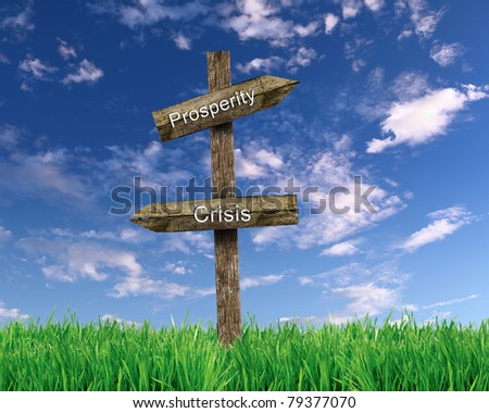 two wooden roadsigns with words prosperity and crisis on them against blue sky